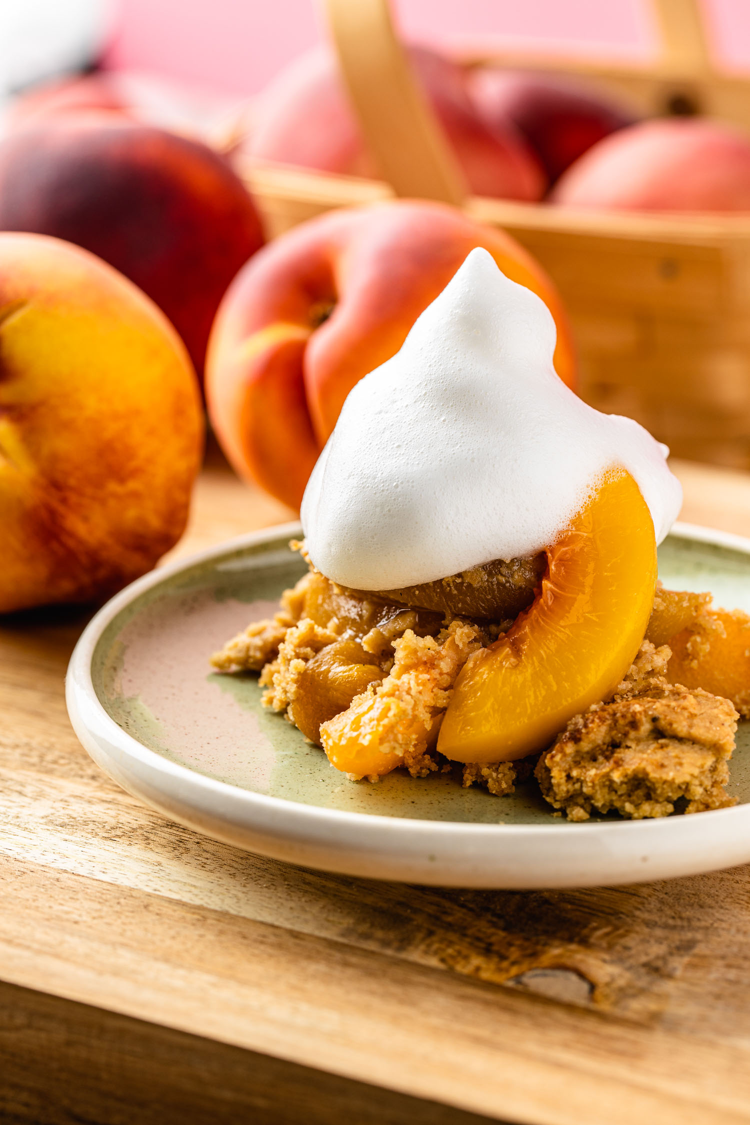 on a mint green mid century modern plate sits a frozen peach cobbler that's gluten free and vegan with a dollo of aquafaba whipped cream and peaches in the background