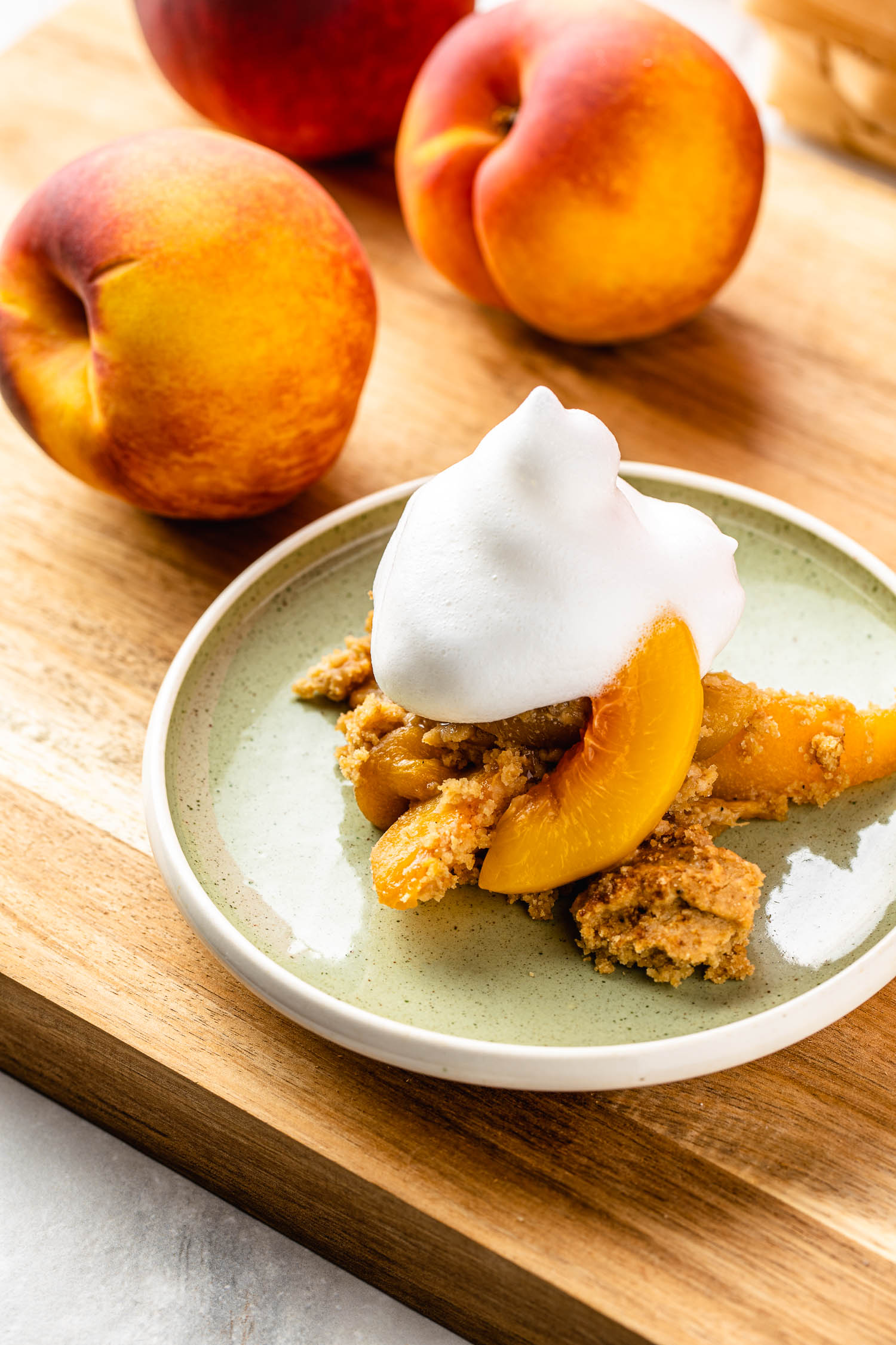 on a wooden cutting board sis two whole peaches and a small green plate holding a serving of peach cobbler with a dollop of aquafaba dairy free whipped cream