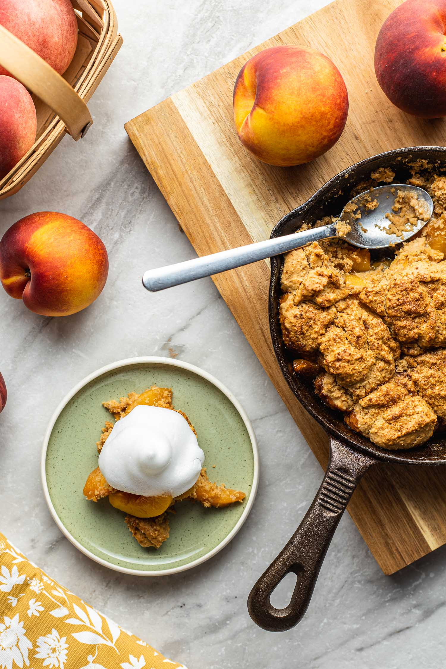 cooking and plating scene of peach cobbler cooked in an iron skillet with a serving plated to the left of the pan with peaches scattered about