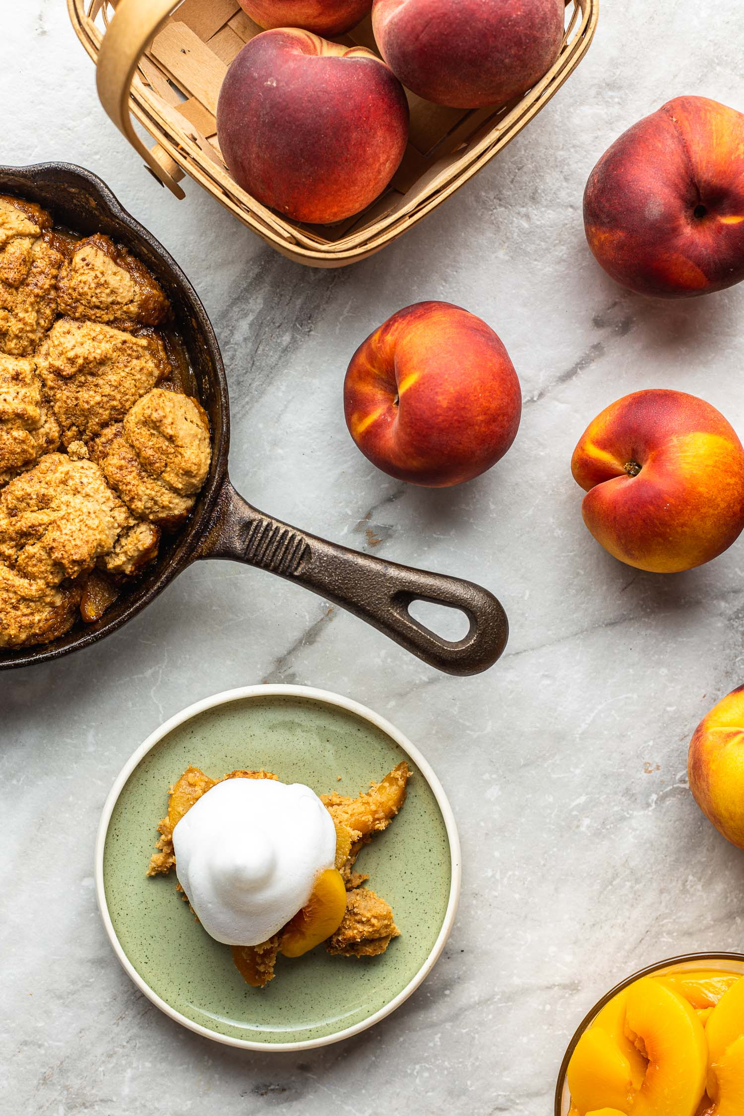 cooking scene on a gray and white marble background with an iron skillet of baked gluten free and vegan peach cobbler, whole peaches, and a serving of cobbler on a mint green plate topped with guit free aquafaba whipped cream