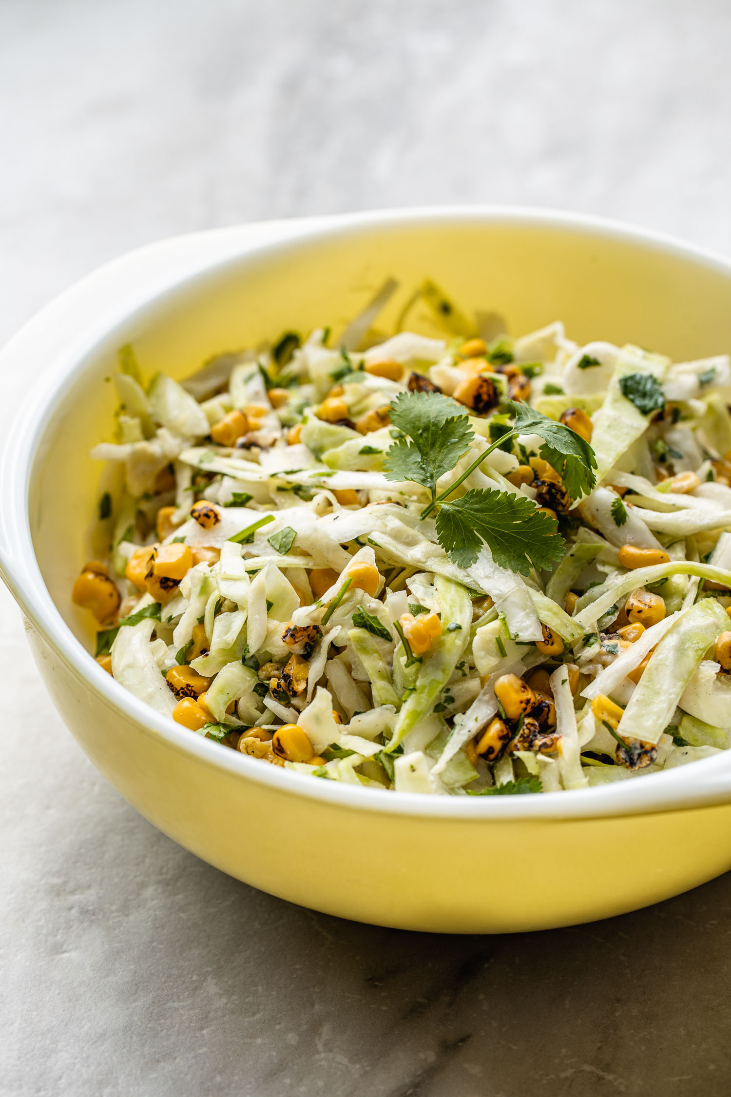 Mexican cabbage coleslaw with corn, cilantro, no mayo, on gray marble background, vintage mid century modern yellow bowl with handles