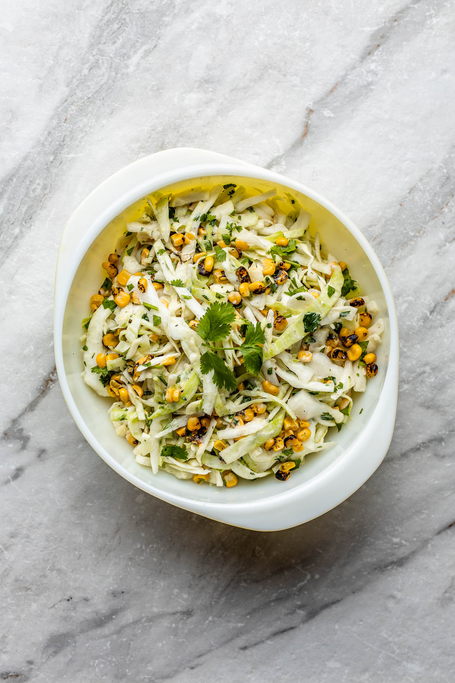 a mid century modern bowl with handles holding coleslaw topped with corn, cilantro, and lime, sits on marble surface