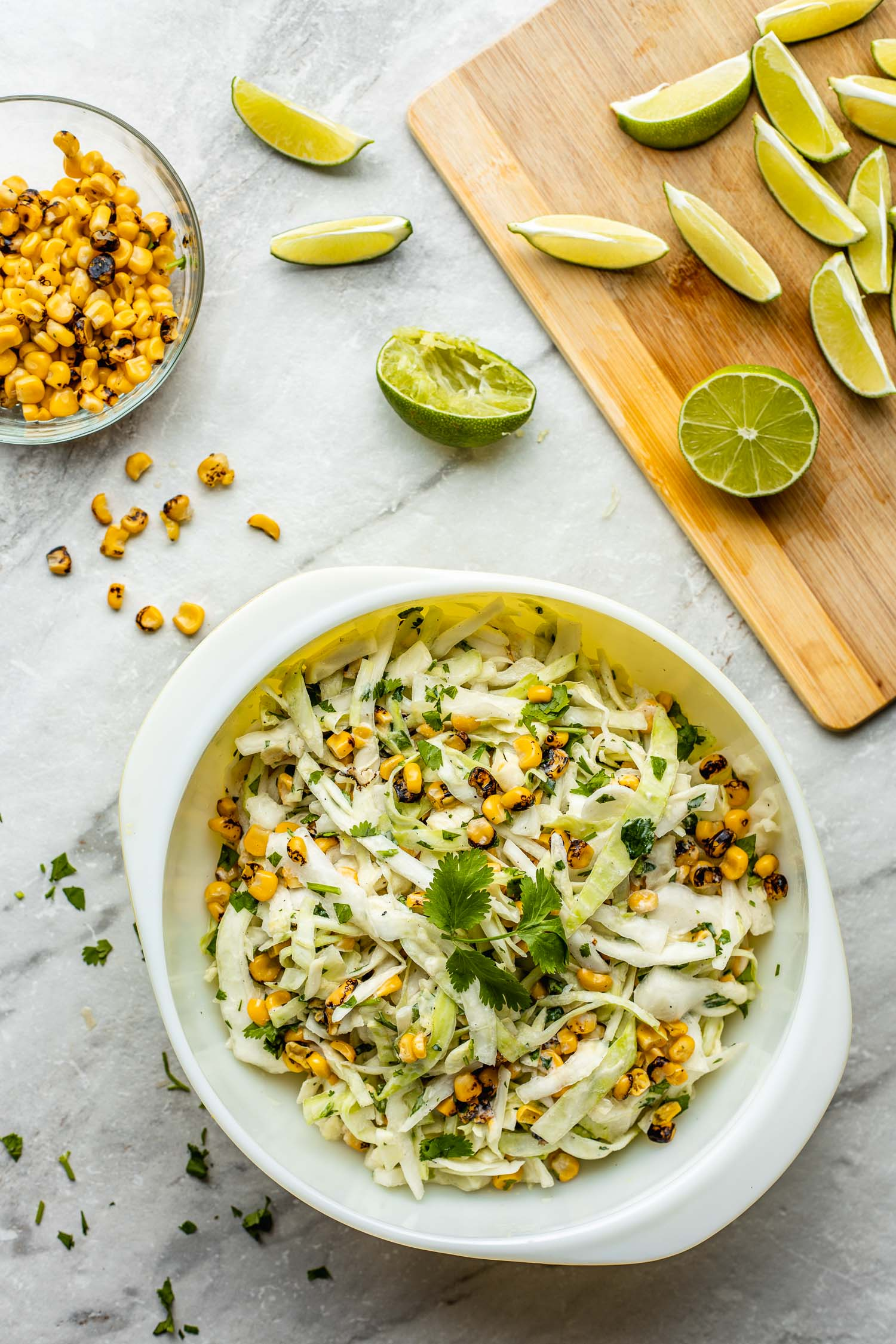 health food cooking scene on white and gray marble with bowl of coleslaw, bowl of blackened corn, and cutting board holding slices of lime, cilantro scattered on marble