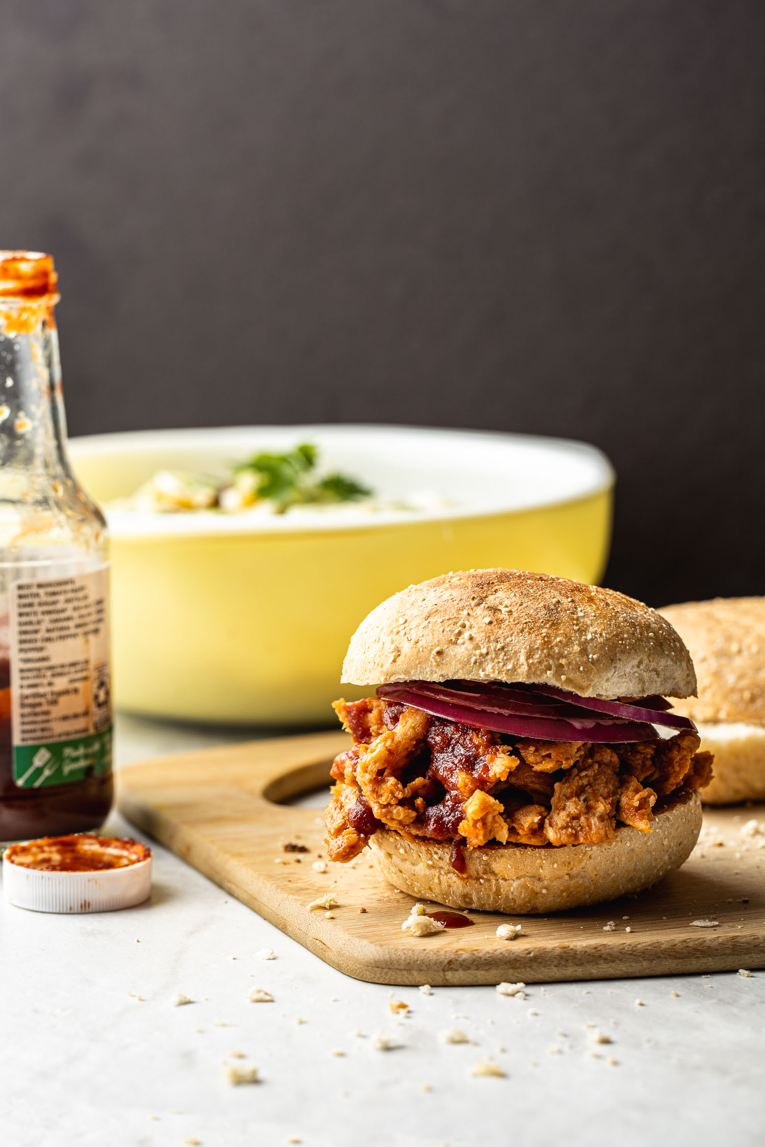 saucy bbq sandwich, butler brand soy curls, meatless bbq, yellow bowl, coleslaw, bottle of bbq sauce