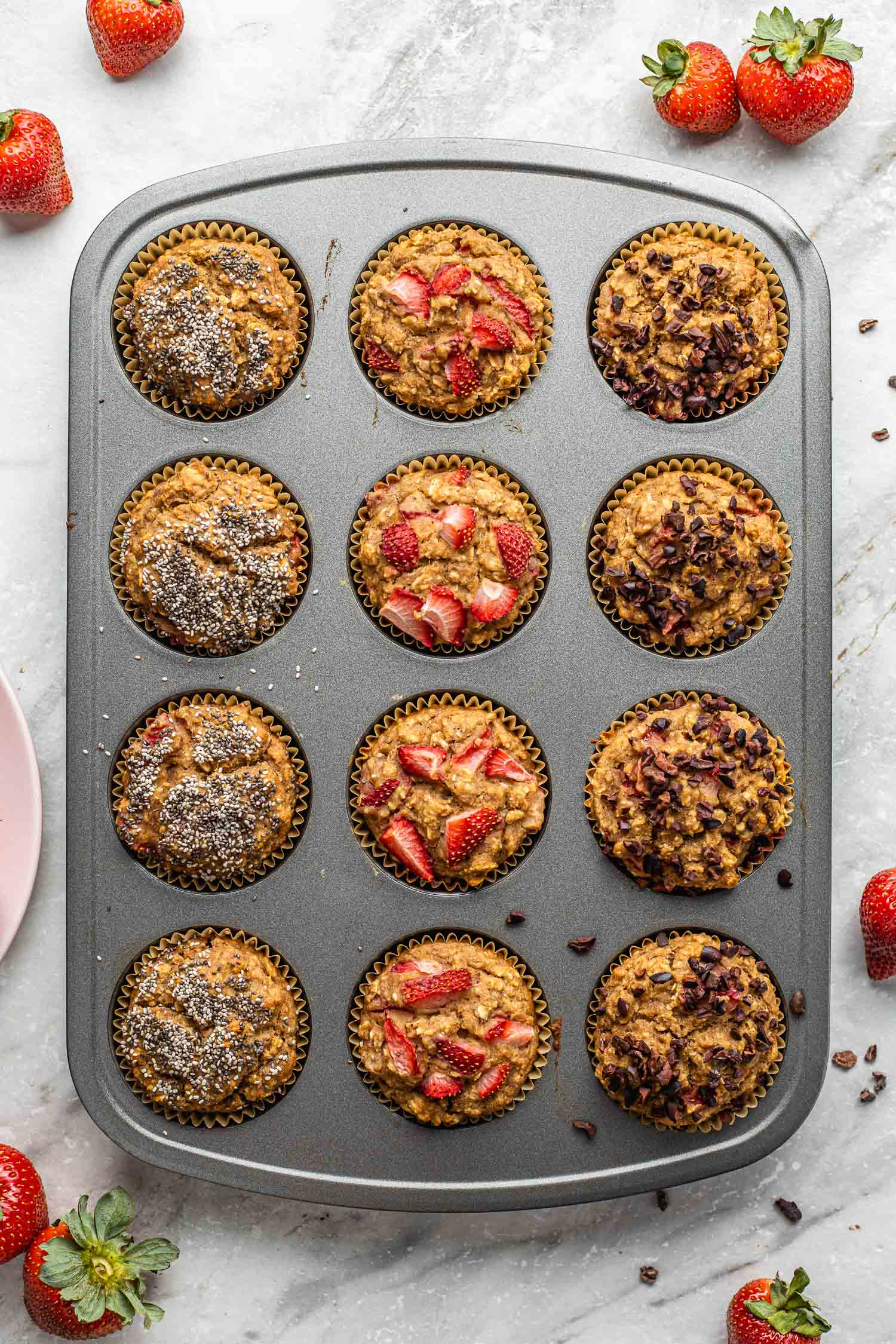 healthy, colorful, strawberry banana muffins sit in a muffin baking pan