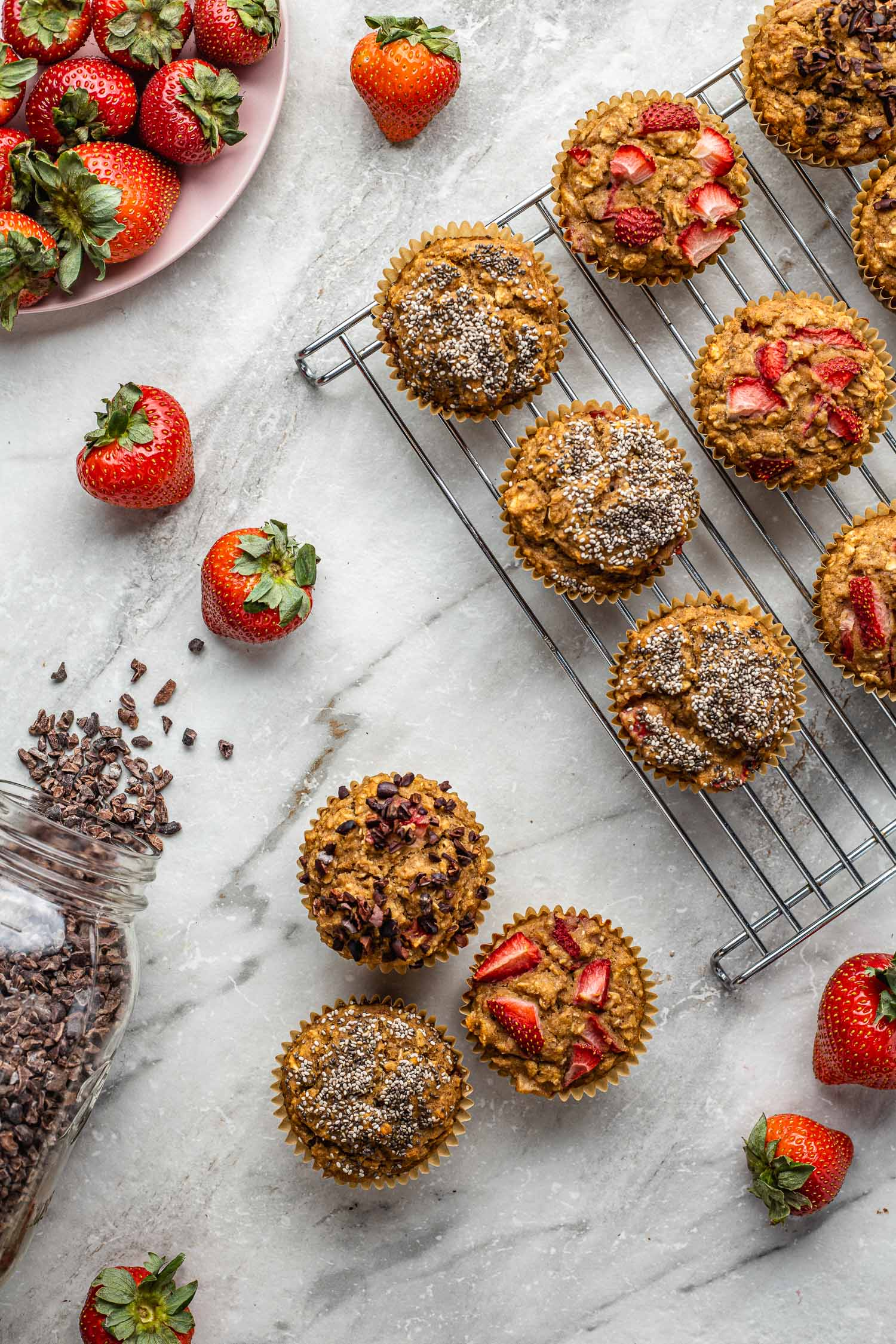 healthy decorated muffins sitting on a marble counter and lined up on a cooling rack