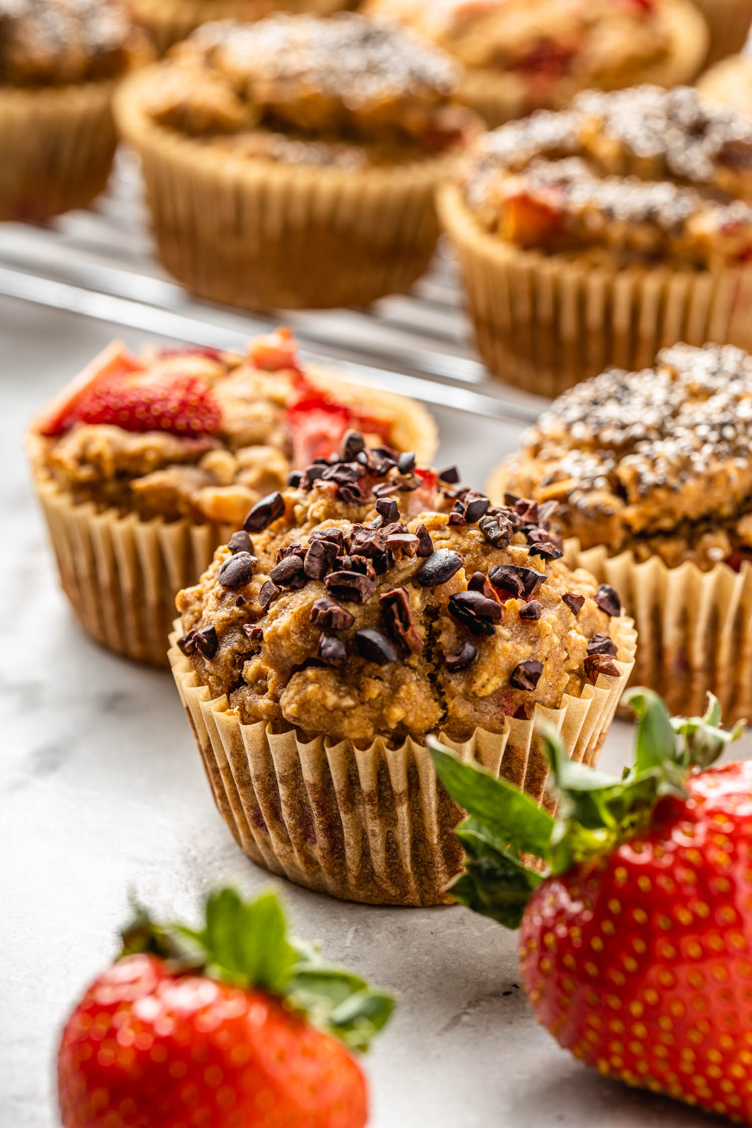 cacao topped vegan, gluten free muffin takes center stage among strawberries and other muffins