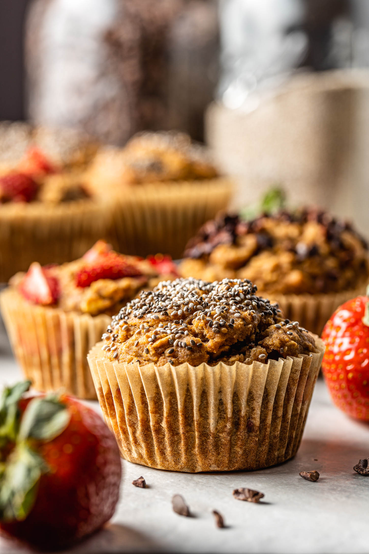 chia seed topped muffin sits in the center of strawberry and cocoa topped muffins