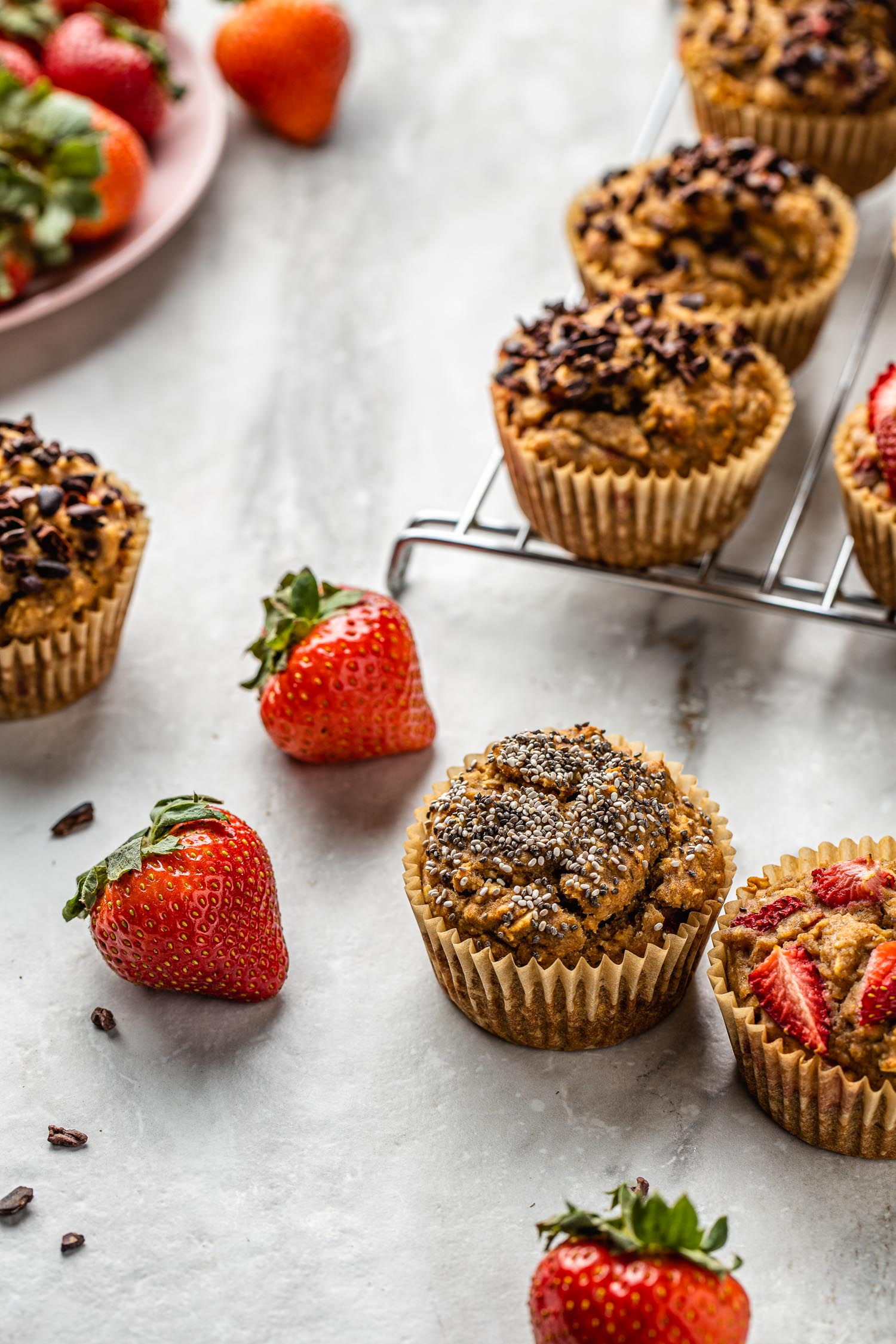 fresh baked muffins cooling on a metal rack and sitting around on a marble surface along with whole fresh strawberries