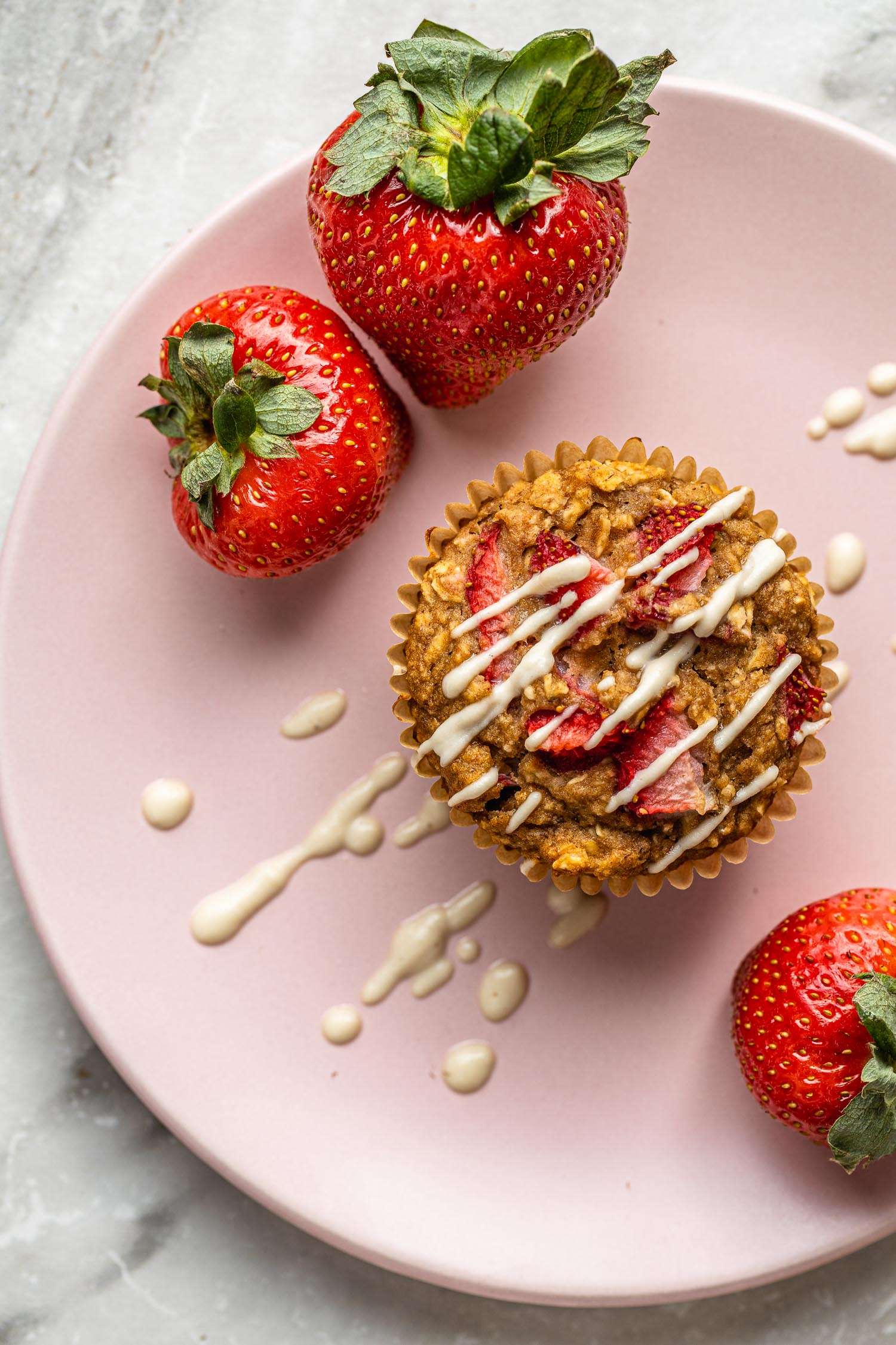 a pink dessert plate holds a healthy strawberry banana muffin drizzled in a dairy free cashew cream glaze surrounded by three whole strawberries