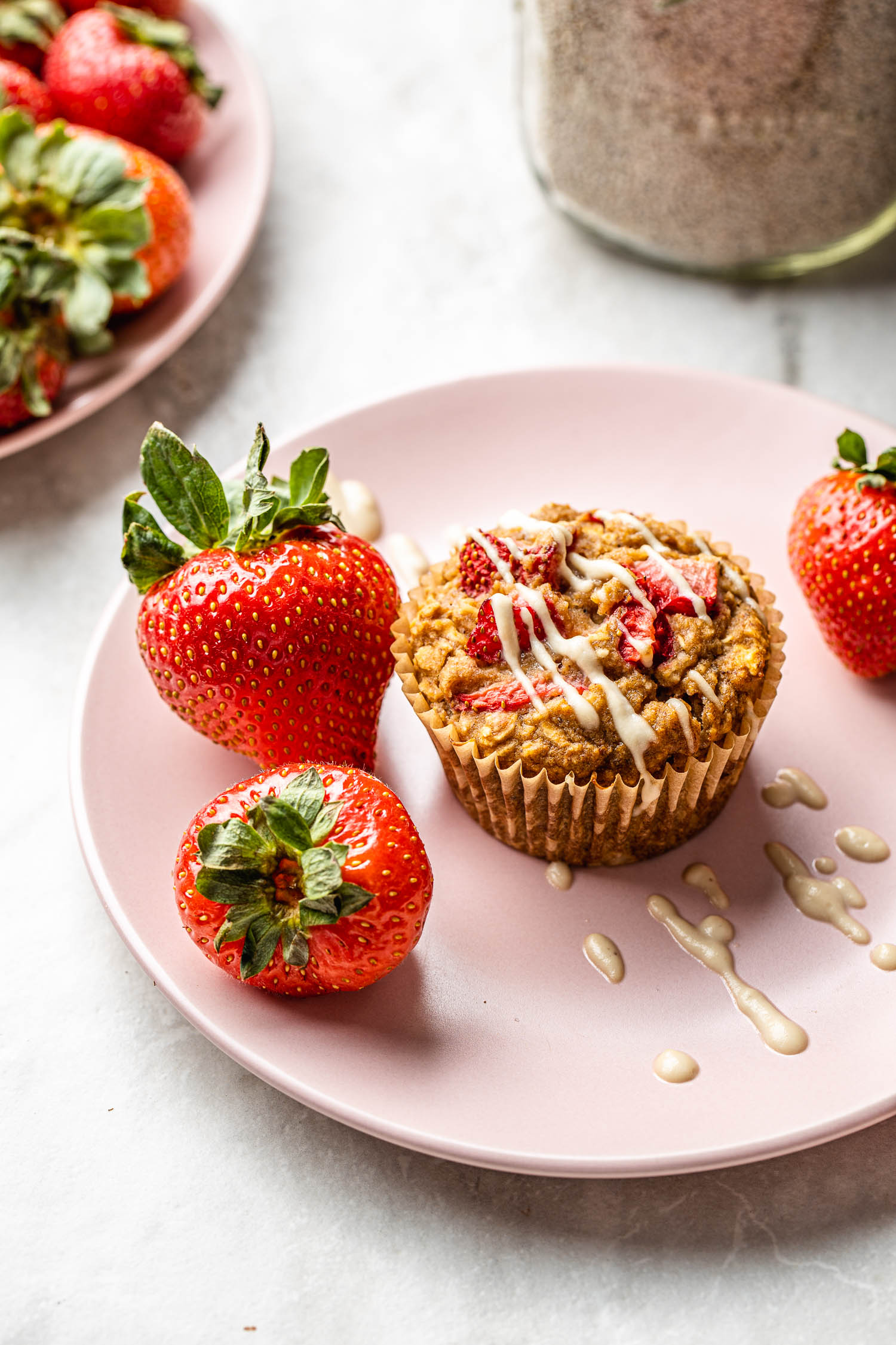 vegan gluten free strawberry muffin on a pink plate with a few whole strawberries with a drizzle of dairy free cream cheese glaze