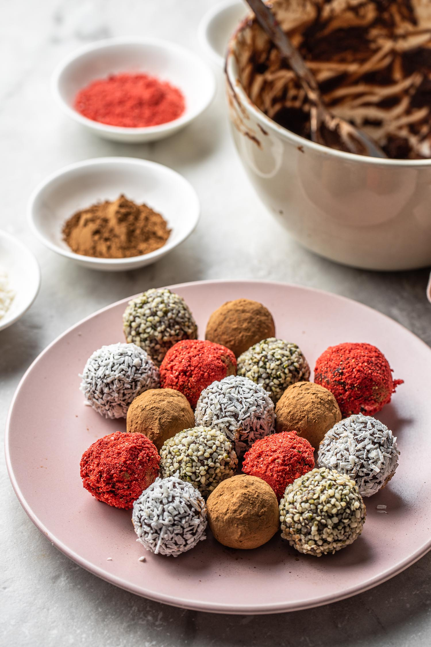 vegan chocolate and avocado truffles candy recipe, truffles coated in red freeze-dried strawberry crumbs, white coconut flakes, brown cocoa or cacao powder, and earthy colored hemp seeds on a pale pink dessert plate with a small bowl of brown cacao powder, red crushed freeze dried strawberries, and an empty used mixing bowl with dark chocolate on the sides