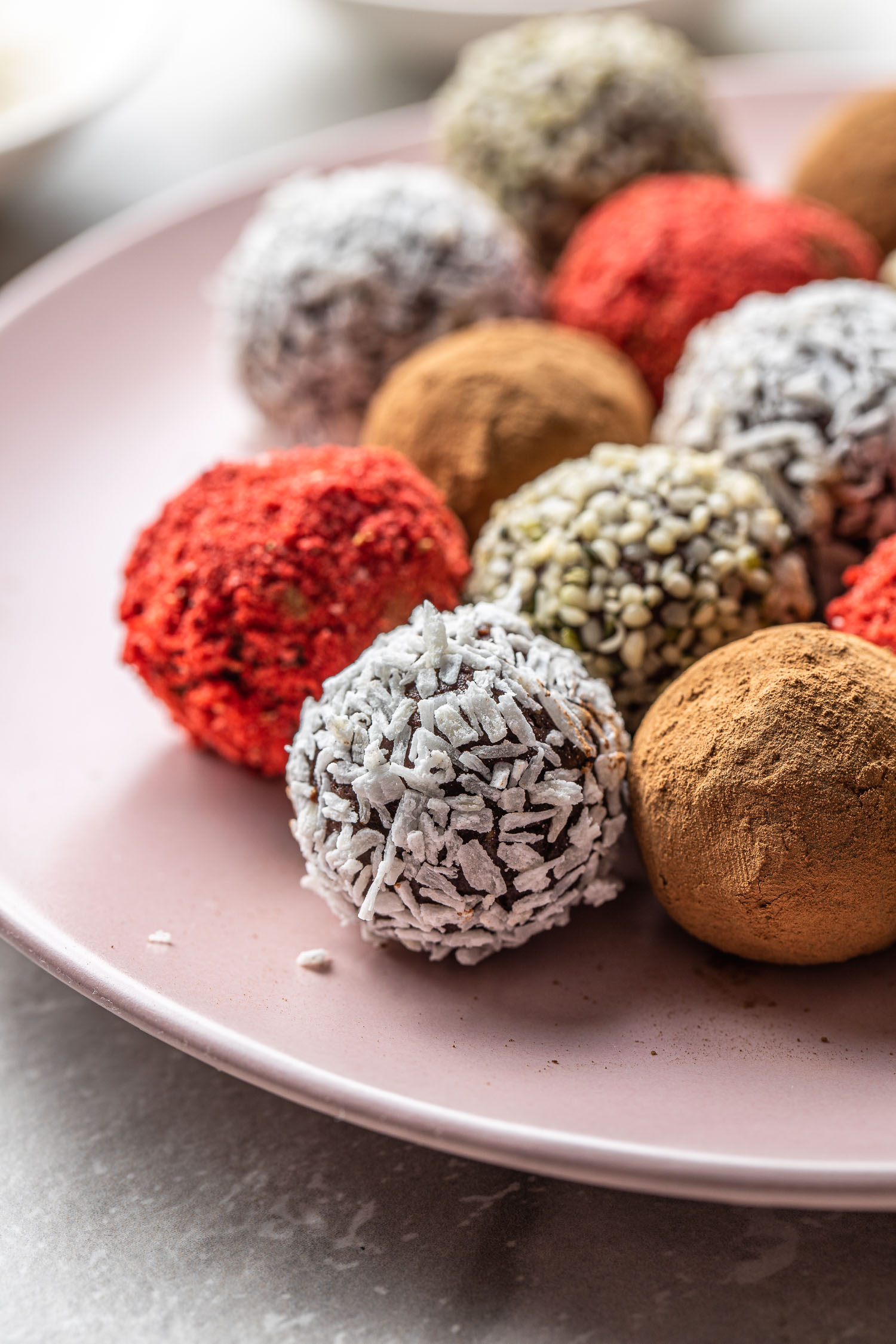 vegan chocolate truffle candy recipe. truffles coated in red strawberry crumbs, white coconut flakes, brown cocoa or cacao powder, and earthy colored hemp seeds on a pale pink dessert plate