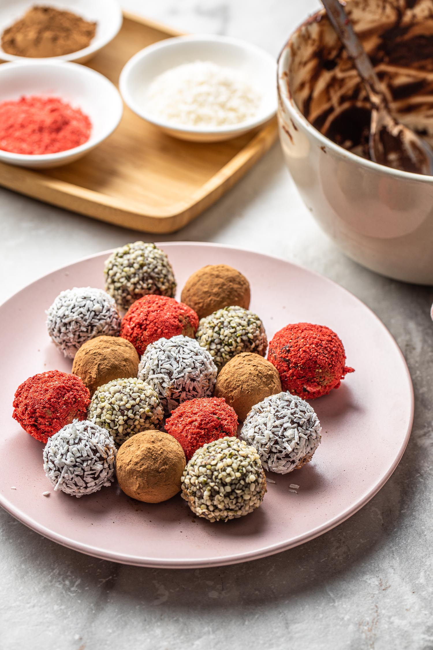 pink plate full of colorful vegan and gluten free chocolate and avocado truffles coated in coconut, hemp seeds, crushed freeze dried strawberries, and truffles coated in chocolate cocoa and cacao powder with toppings in bowls to the back