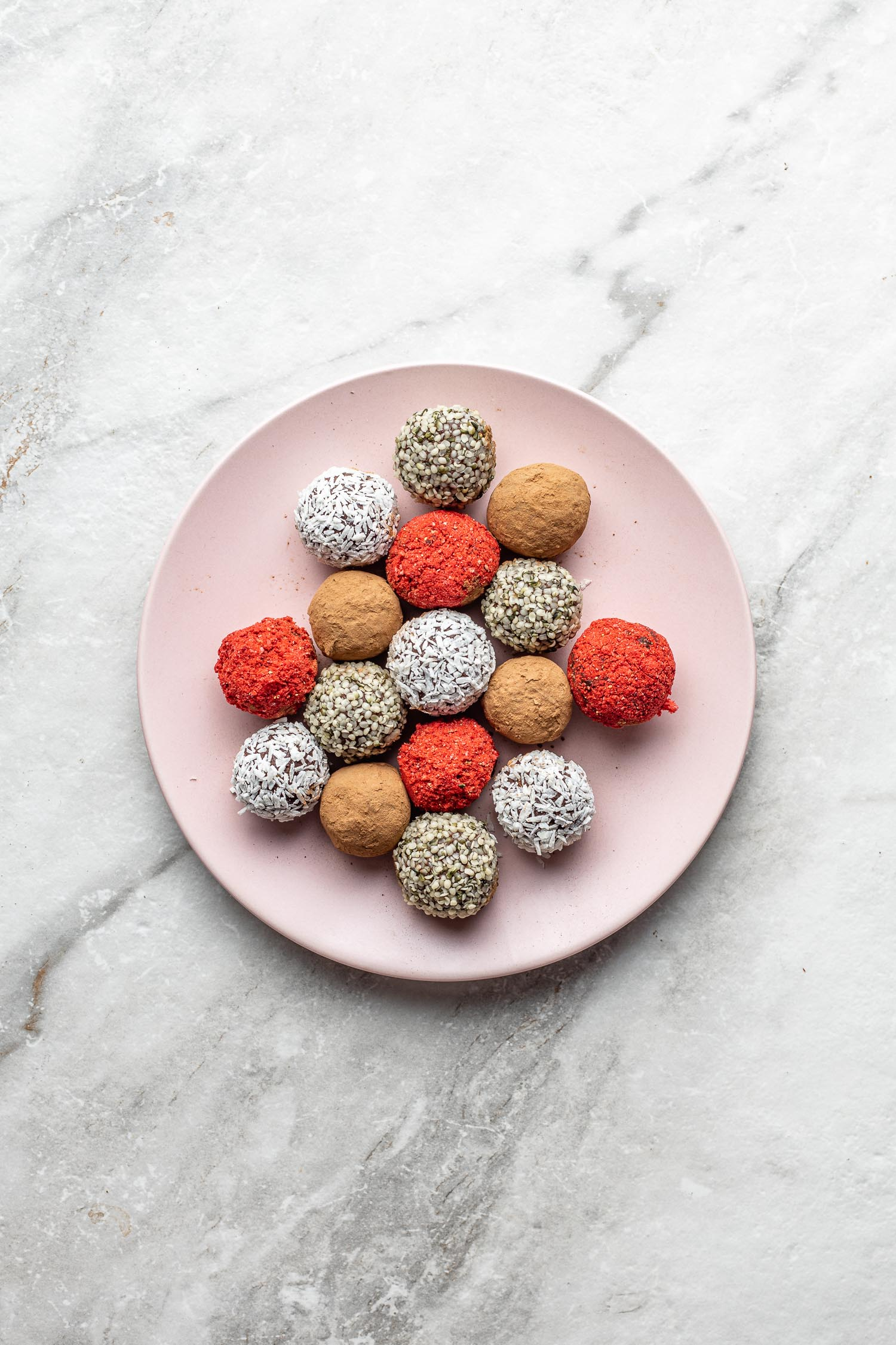 on a marble background sits a pink plate filled with red, white, brown and seeded vegan chocolate and avocado truffles