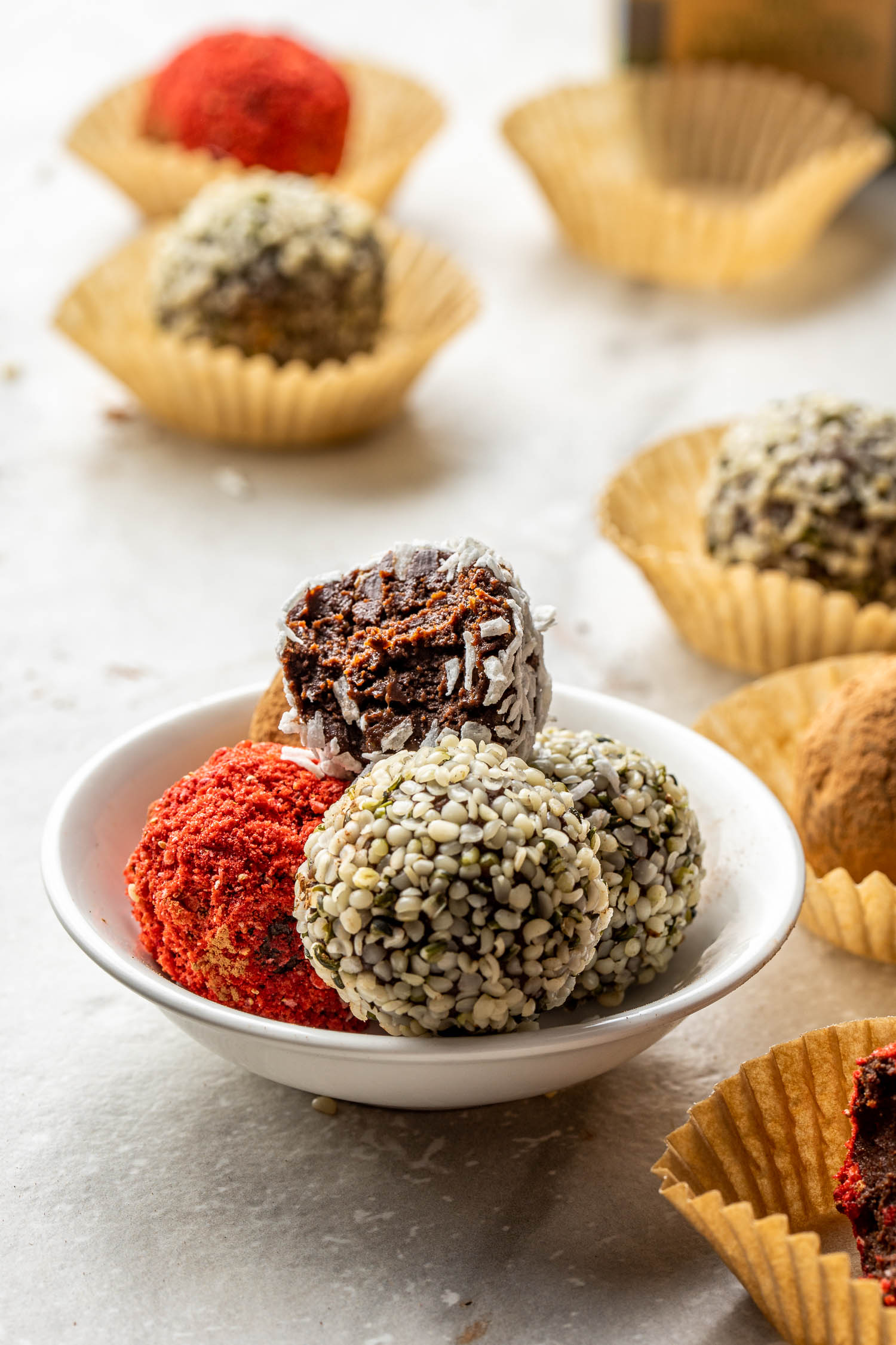 vegan chocolate truffles with a variety of toppings in a white glass bowl along with all sorts of truffles sitting in brown parchment paper cupcake liners