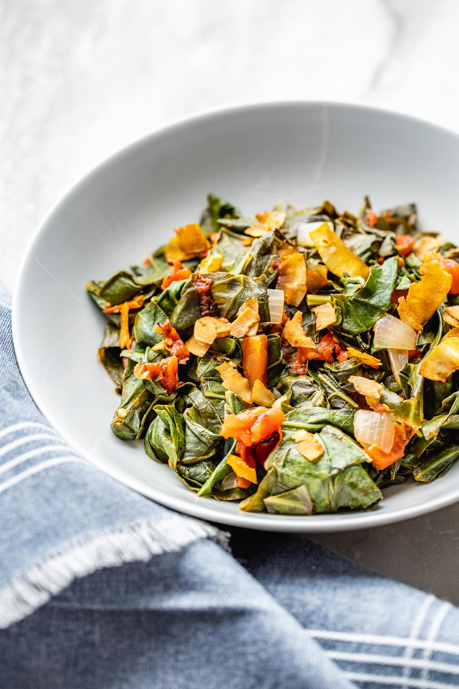 a blue fringed napkin is gathered beside a white shallow glass bowl of a hearty, vegetarian collard greens recipe with a smoky meatless topping