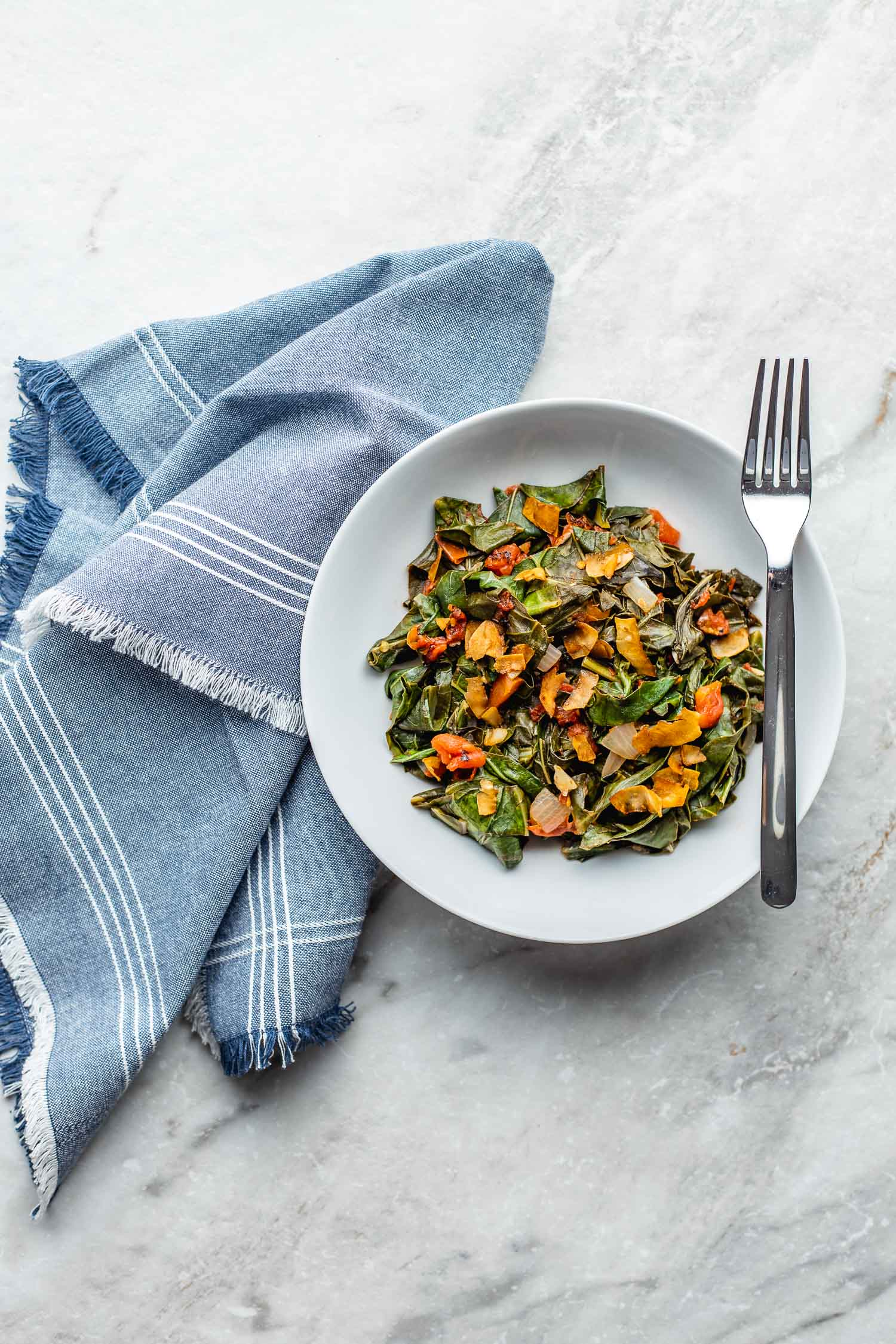 on a marble countertop, sits a blue cloth napkin next to a white bowl of quick collard greens with a fork laid across the top of the bowl