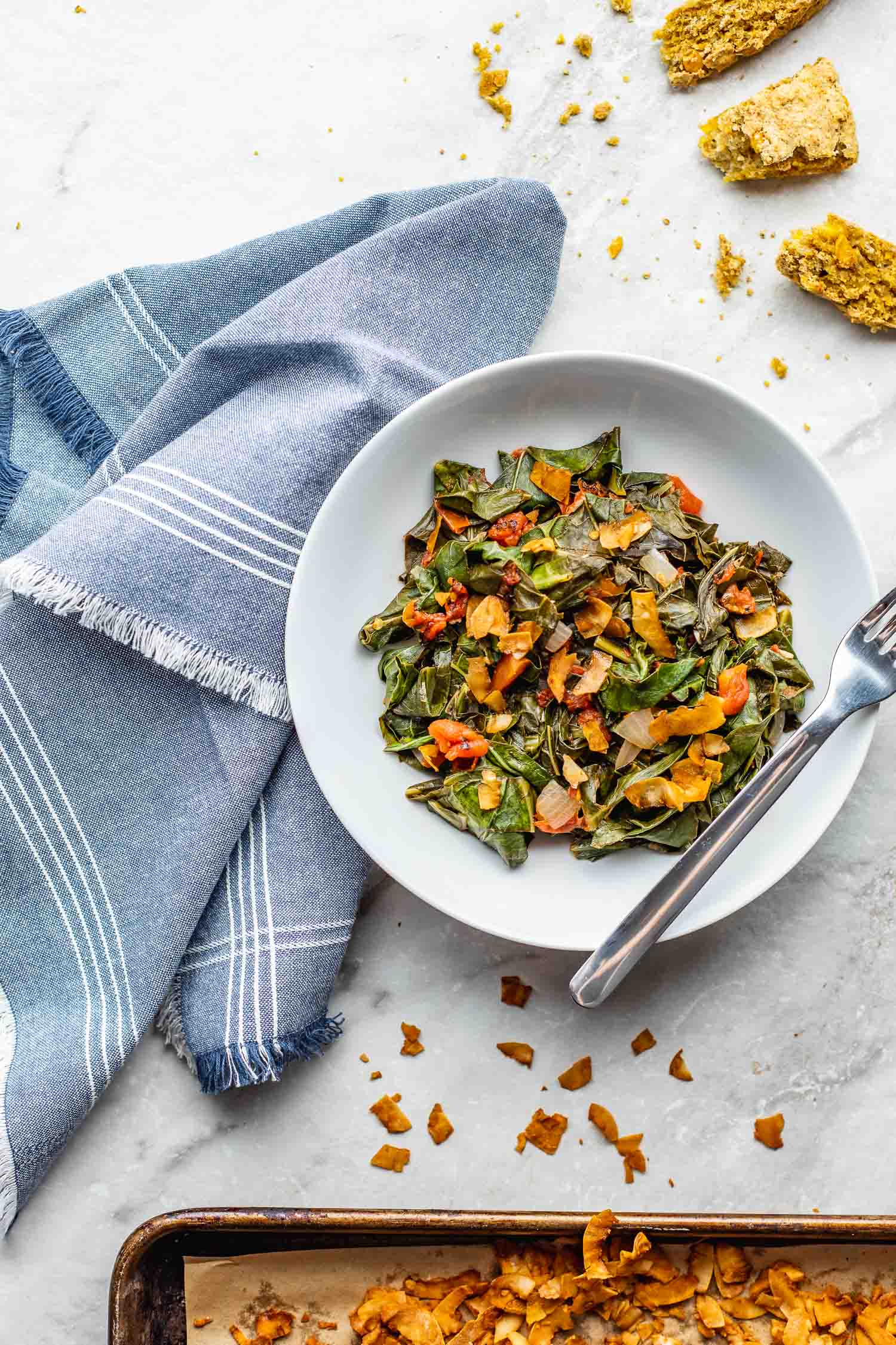a pan of oven baked vegan bacon sits near a bowl of southern-style collard greens witha few pieces of cornbread scattered around on a white marble counter surface