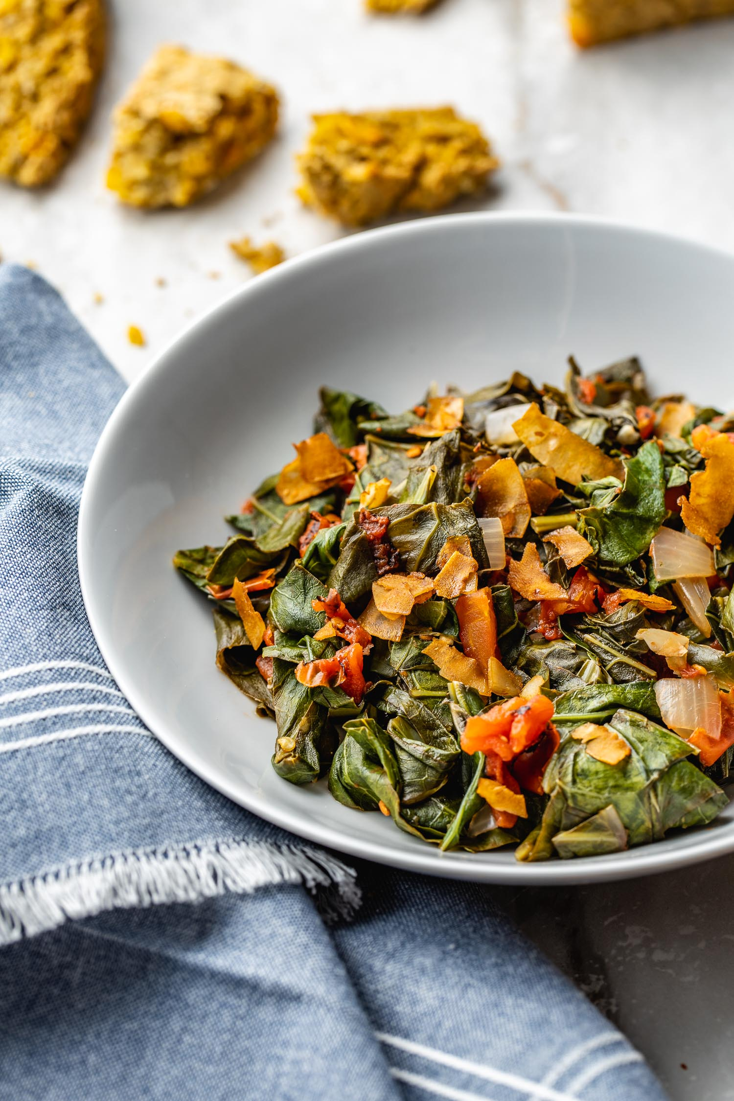 a shallow white bowl of southern-style collard greens with bits or cornbread scattered beside it along with a blue denim cloth napkin