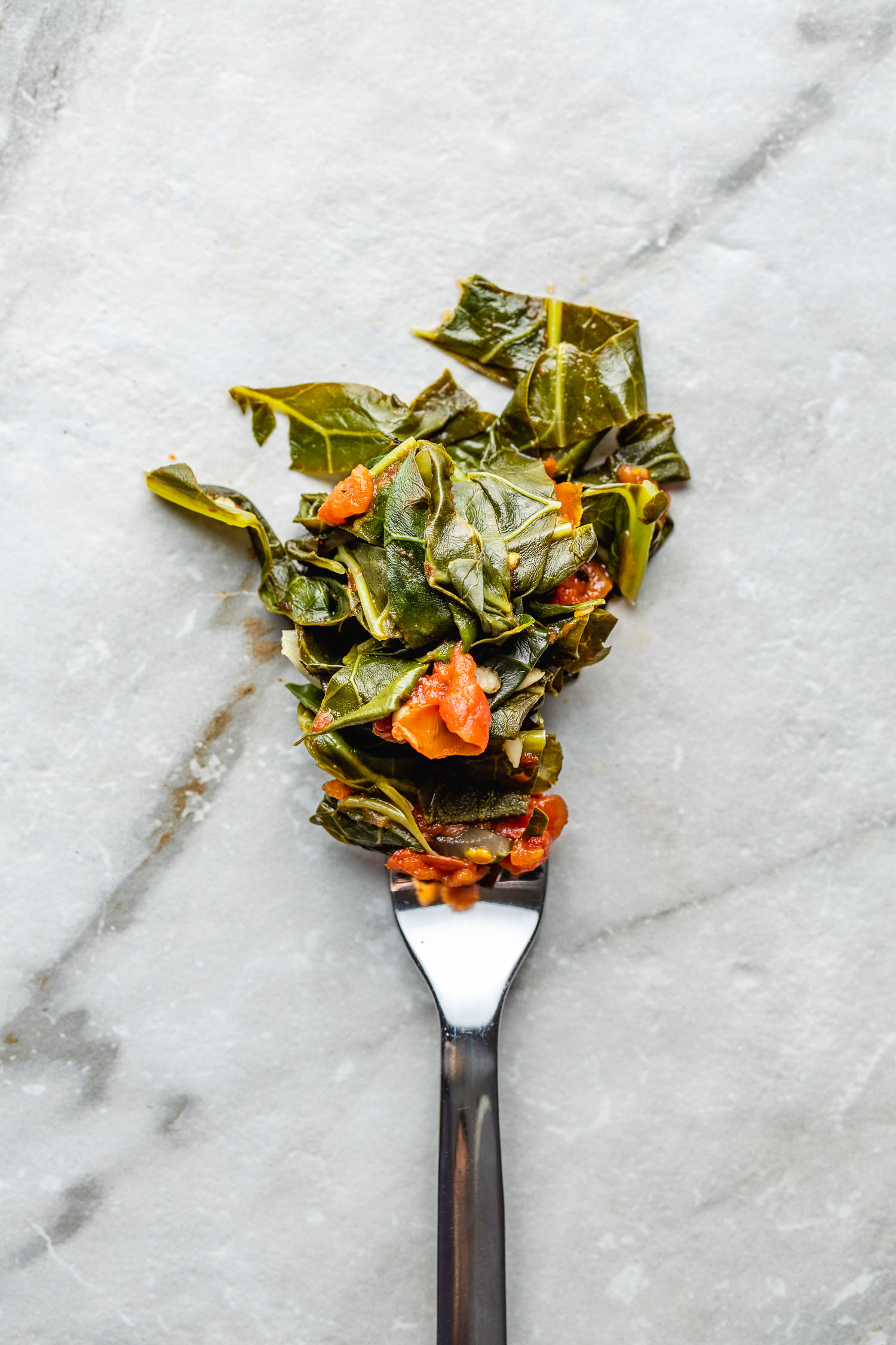 on a marble counter sits a single fork filled with bite of vegan collard greens recipe
