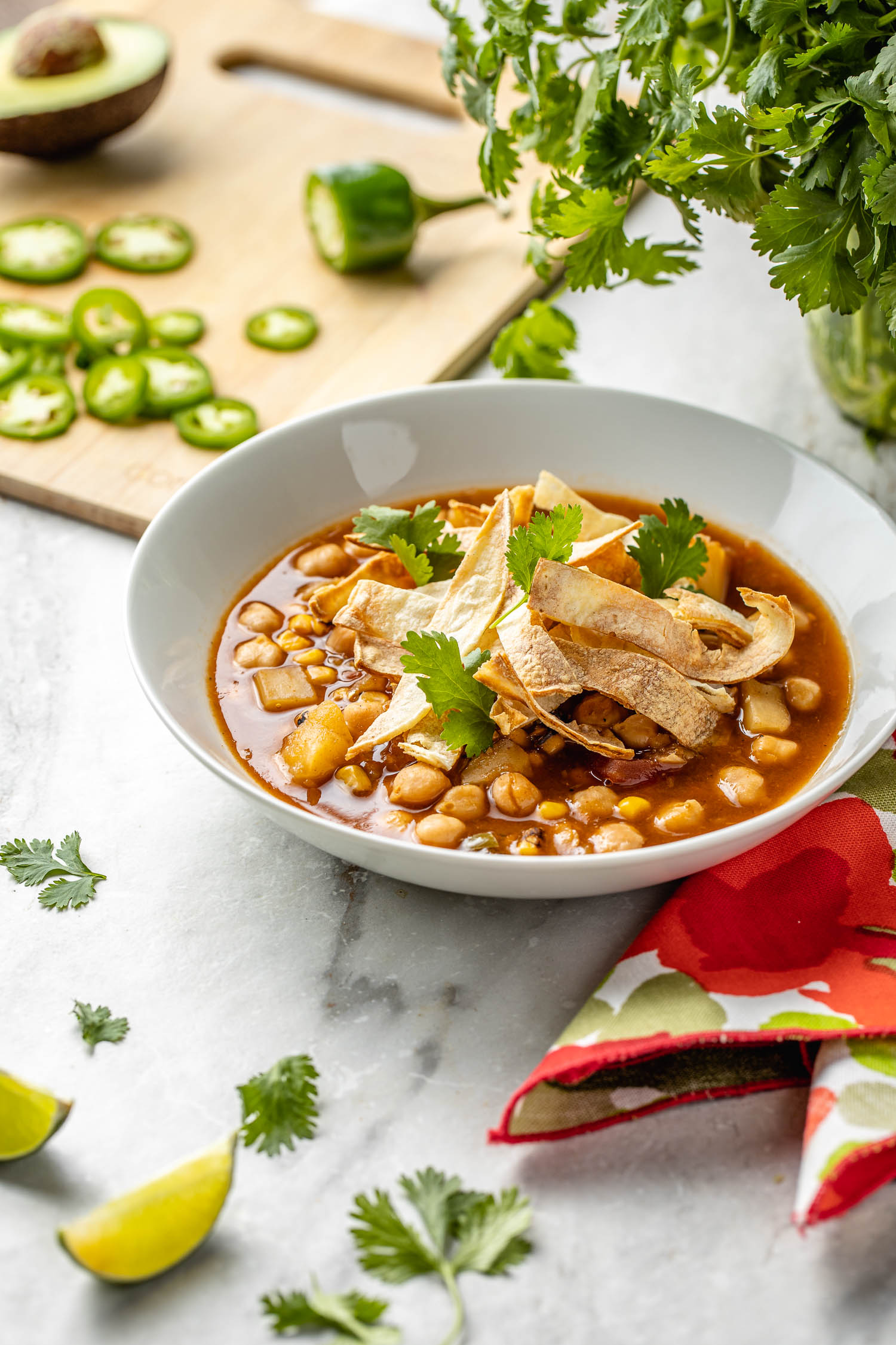 white bowl of authentic tortilla soup recipe topped with strips of corn tortilla chips and cilantro, lime wedges, green herbs, and jalapeno peppers and avocado scattered around the soup, red napkin