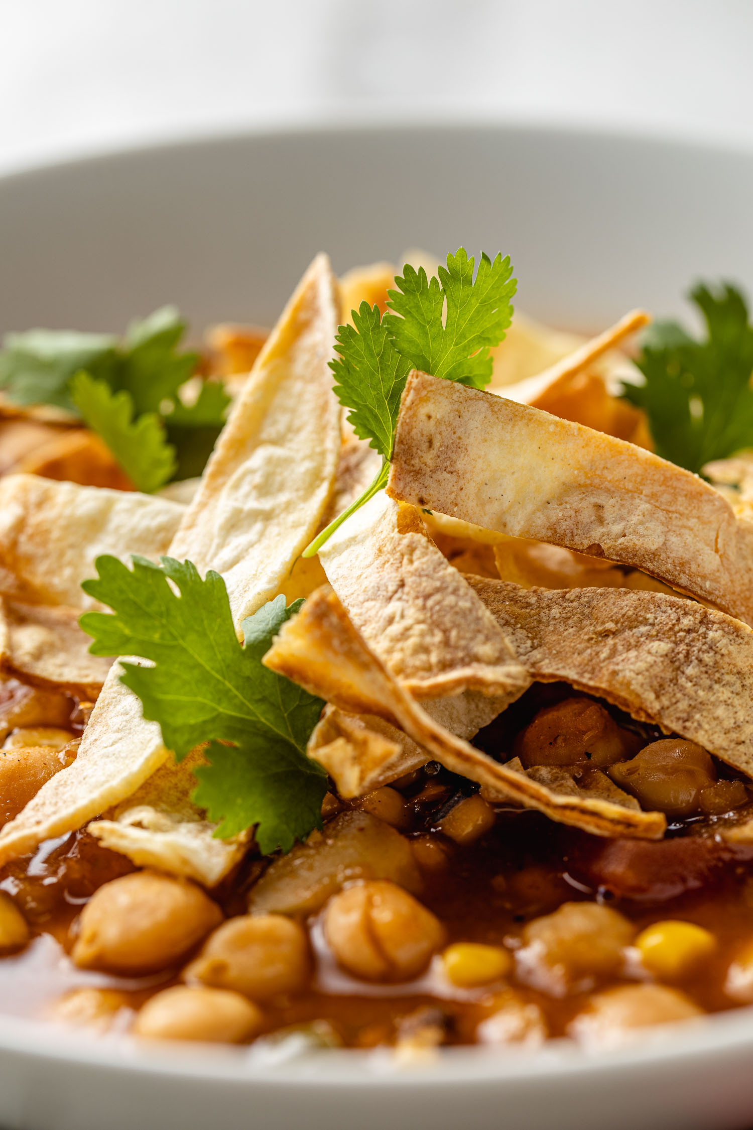 strips of oil free tortilla chips sit  on top of vegan tortilla soup with chickpeas with leaves of cilantro on top of the chips