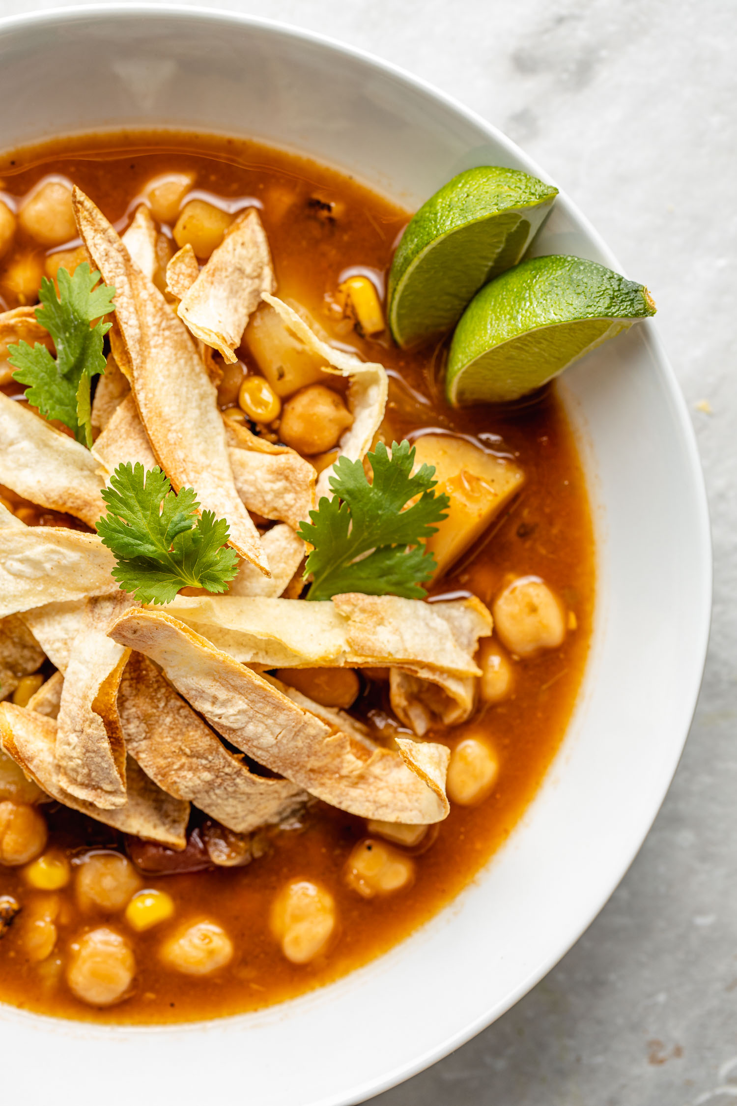 white bowl of red vegan tortilla soup in white bowl topped with strips of corn tortilla chips, cilantro leaves, green lime wedges
