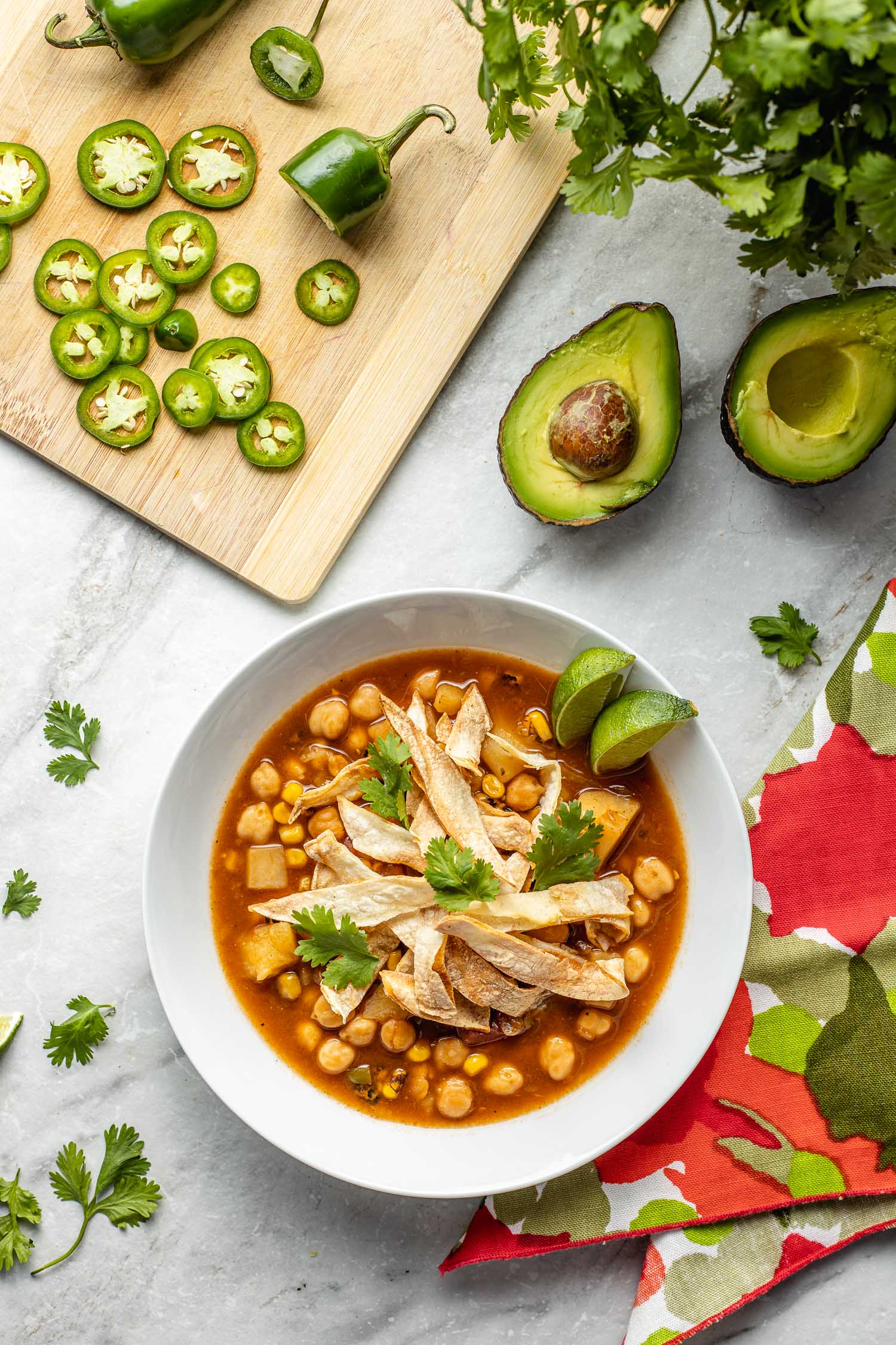 vegan Mexican tortilla soup in a white bowl topped with tortilla chips, cilantro, red print napkin to the side, sliced cutting board of jalapeno peppers, sliced avocado with pit
