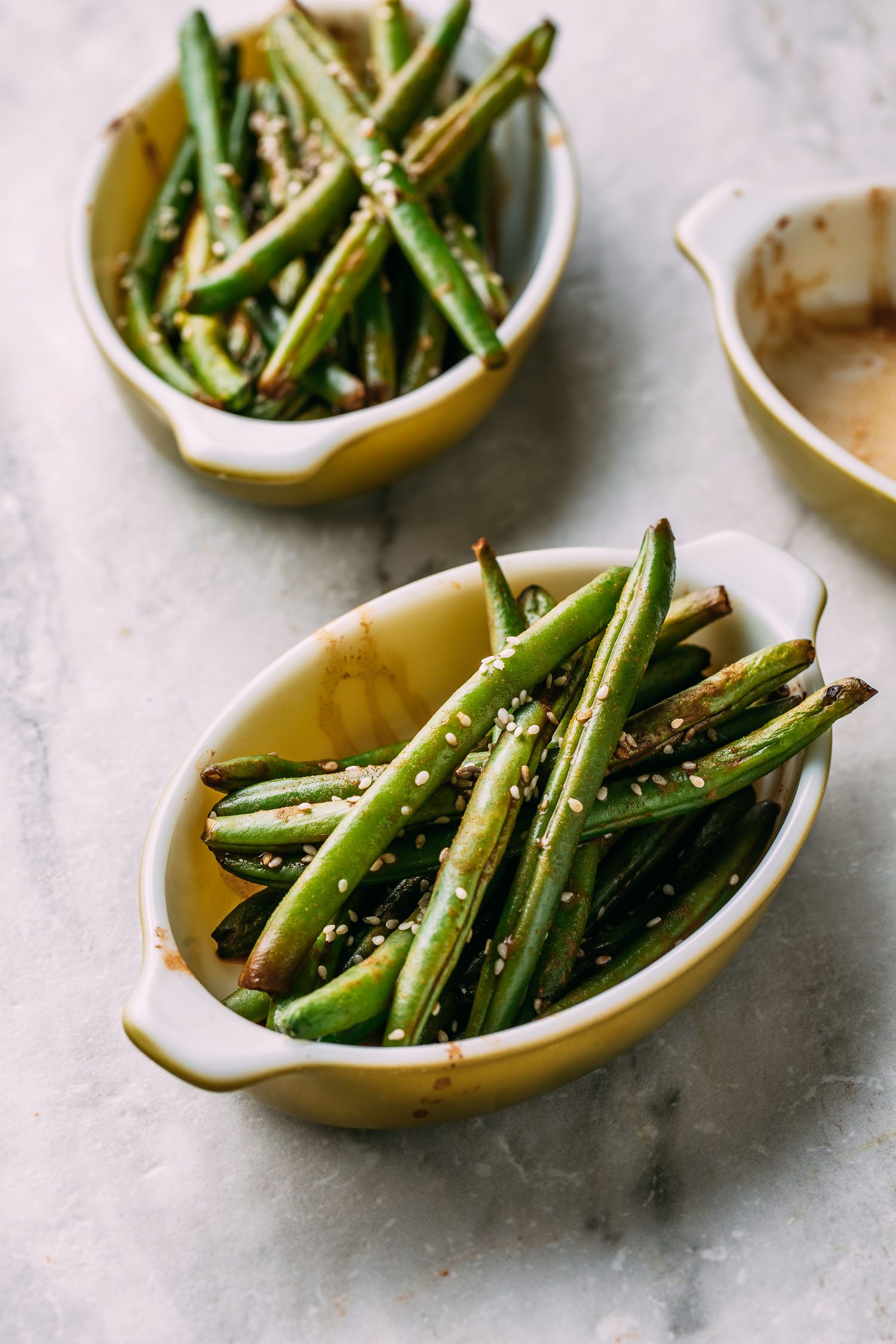 three mid century modern avocado green colored baking dishes with two holding roasted string beans topped with sesame seeds sitting on marble