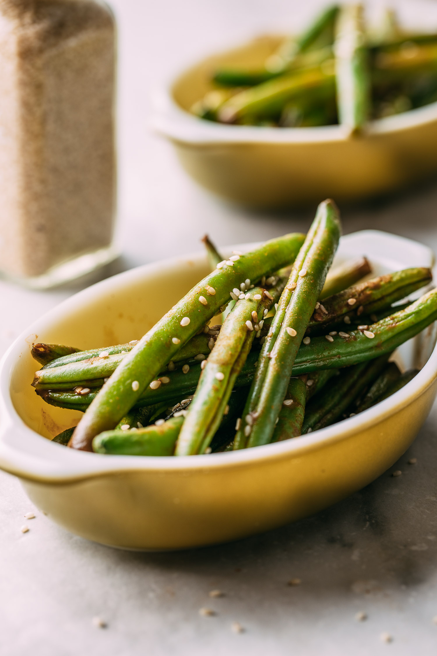 a glass jar of ground ginger sits between two oval serving dishes filled with broiled and pan cooked green string beans with sesame seed topping