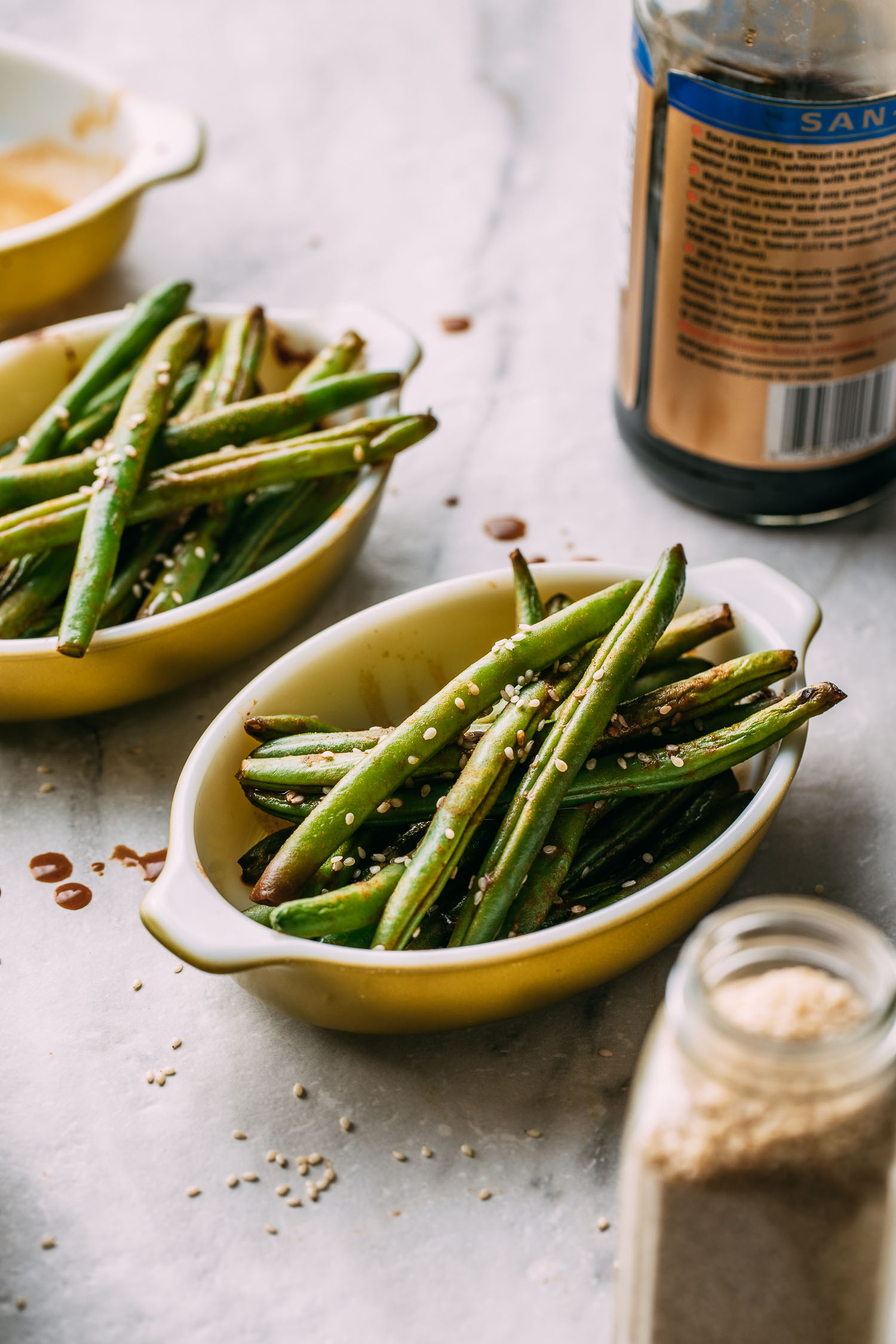 an open jar of garlic powder, a bottle of tamari soy sauce, and two oval dishes of roasted green beans with sesame seeds