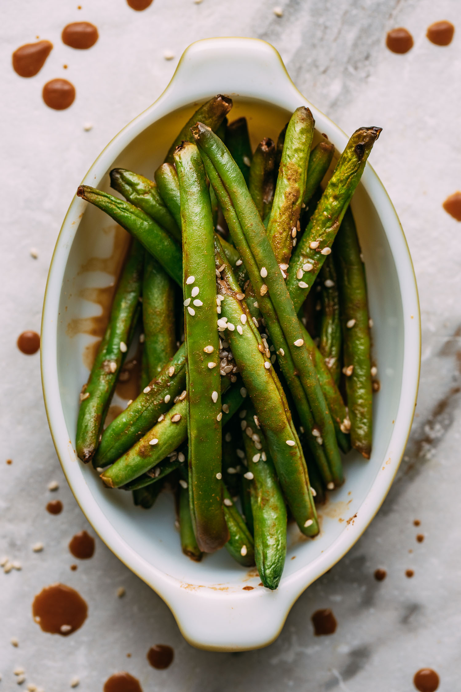 an oval shaped vintage baking dish with pan cooked green beans drizzled in a tahini sauce and sesame seeds with drips of sauces around the dish of beans