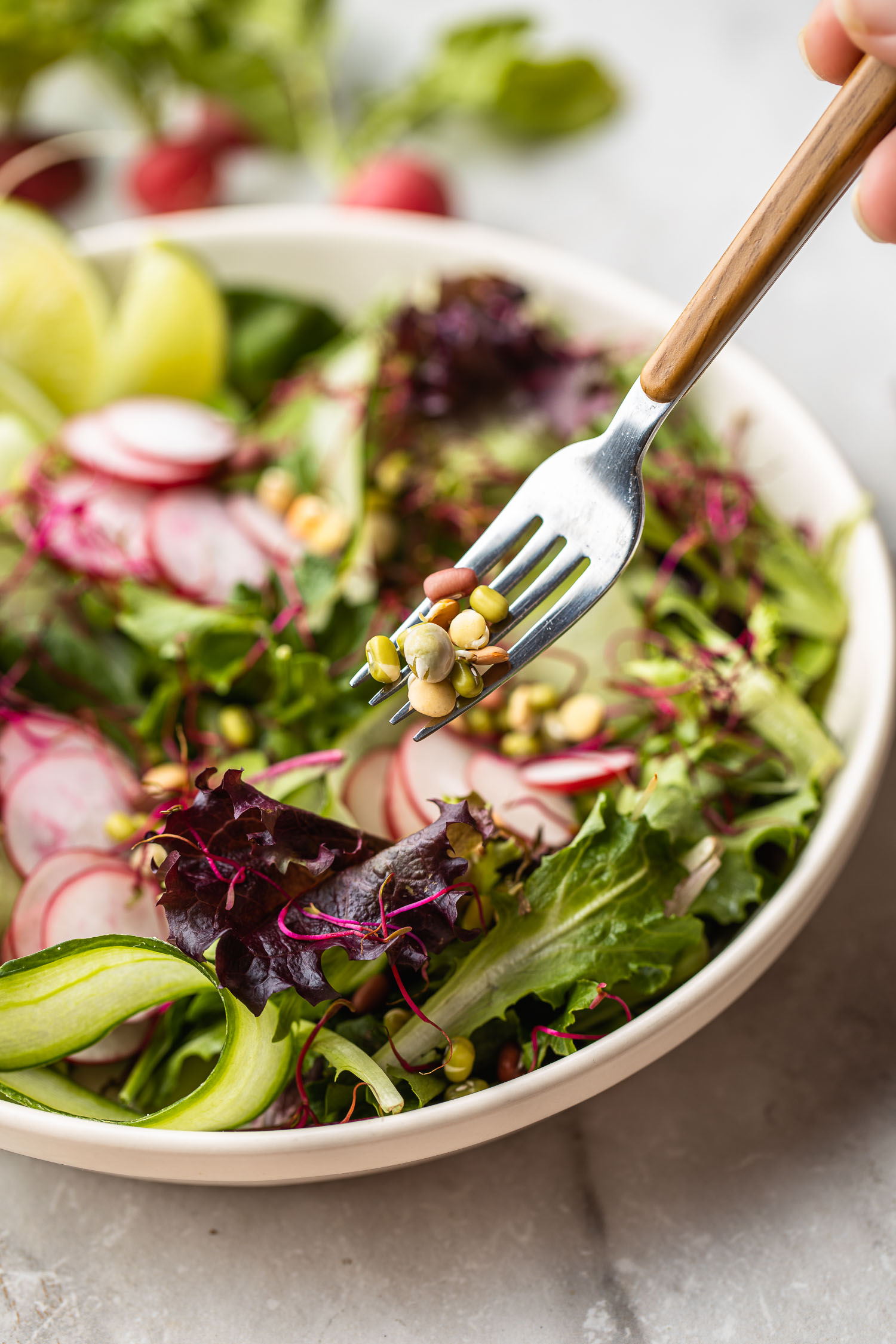 fork going into bowl of simple side salad with colorful radish, ribbons of cucumbers, and sprouts