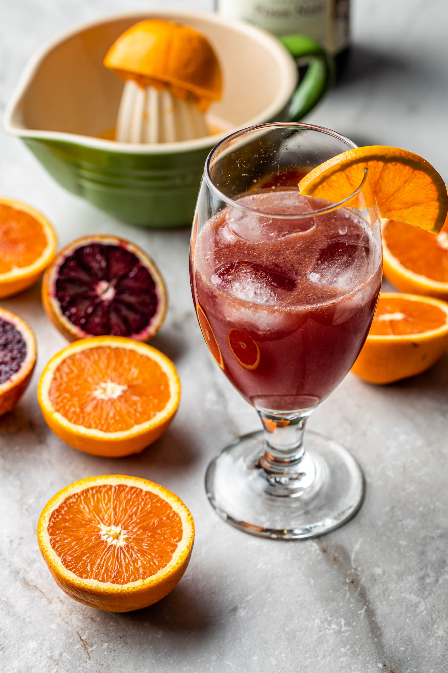 a purple red colored wine cocktail with fresh orange juice