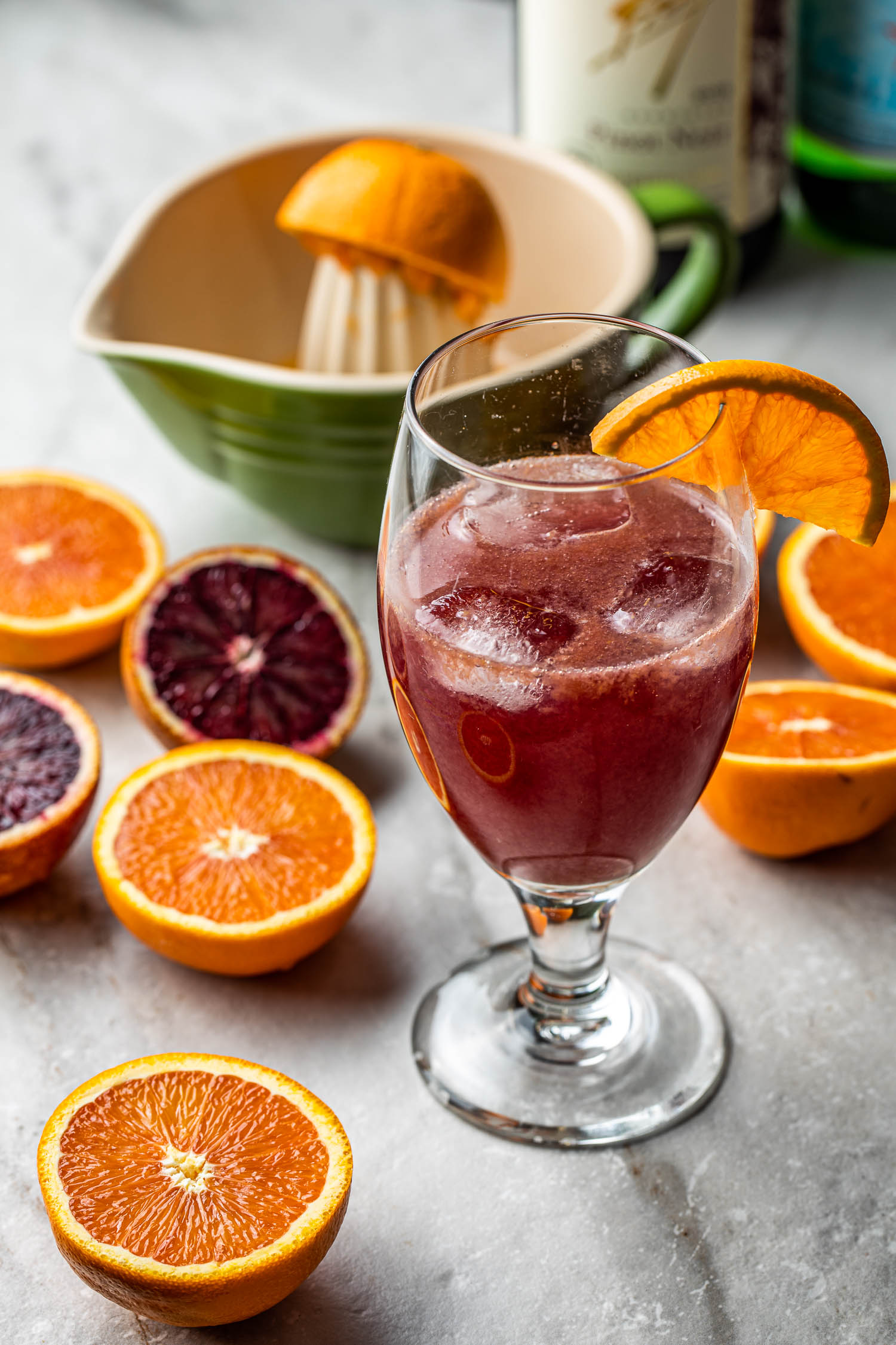 oranges being juiced for a skinny wine spritzer mixed drink