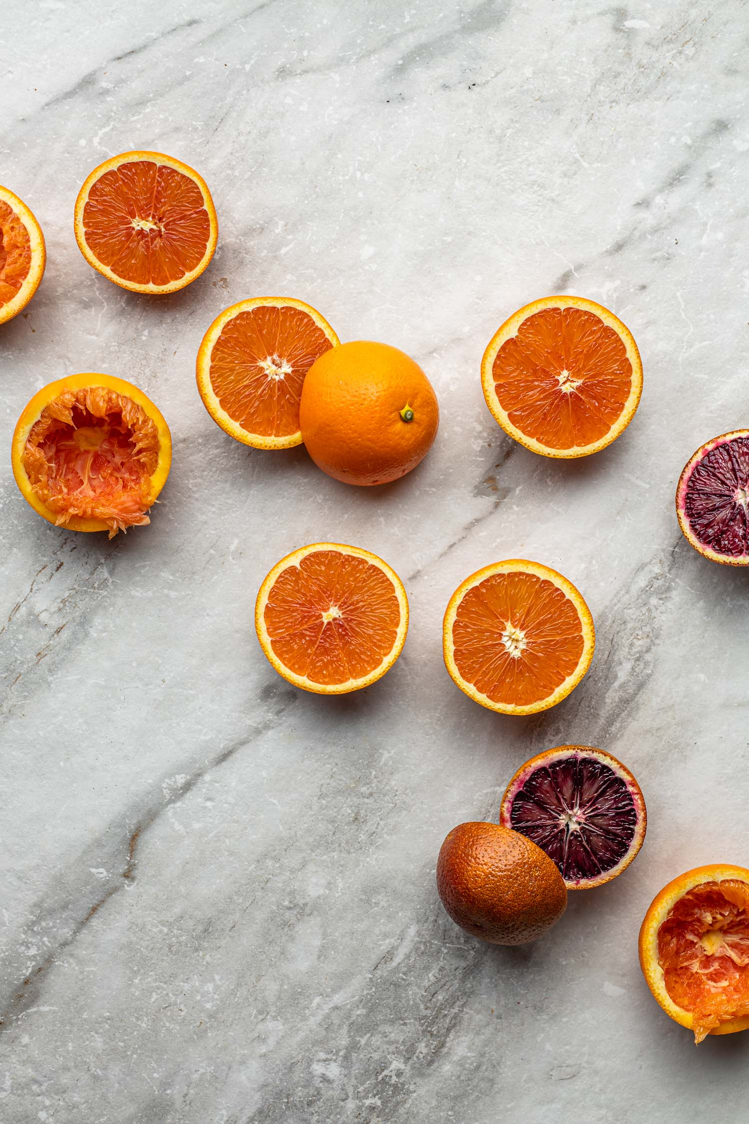 oranges sliced in half, including a couple of blood red oranges