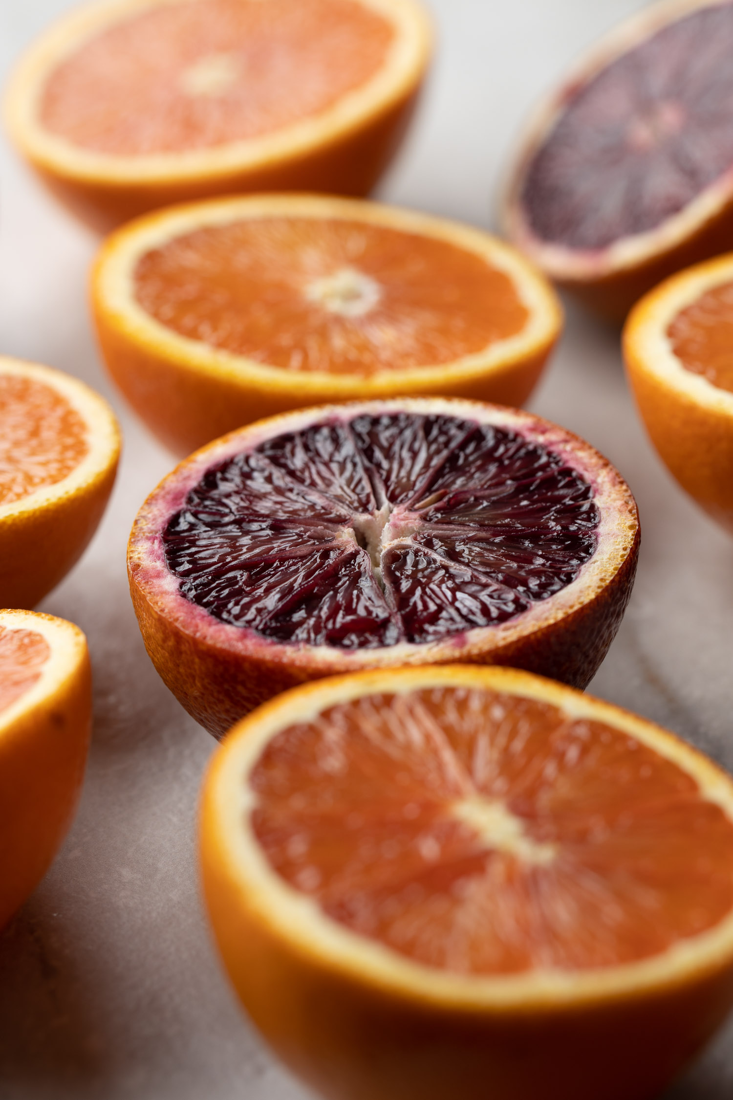 red blood oranges and regular oranges sliced in half